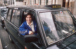 Female taxi driver leaning out of cab window smiling,
