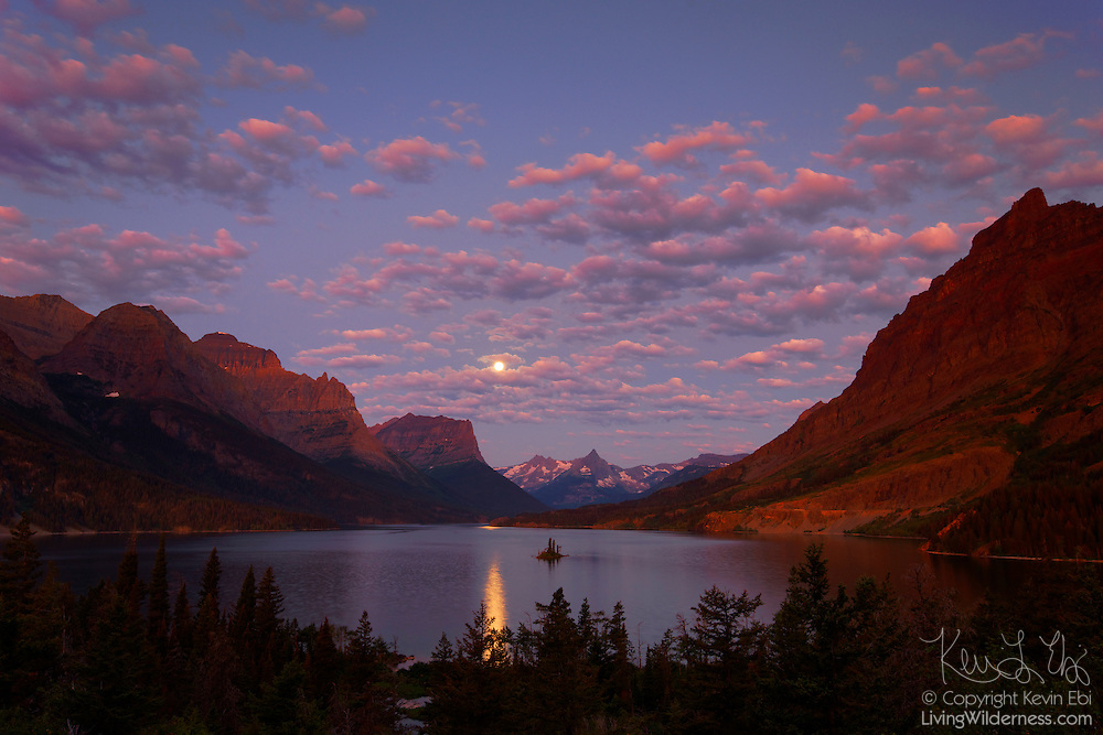 The full moon sets over St. Mary Lake as the first light of day reddens the skies over the Rocky Mountains and Glacier National Park, Montana. Wild Goose Island is visible to the right of the moon's glint near the center of the lake.