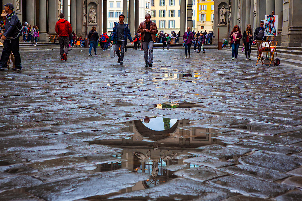 Reflections in rain puddles, Piazzale degli Uffizi, Florence, Italy