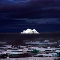 Pure white iceberg which looks as though it is lit up with a spotlight.  The photo was taken in Greenland.