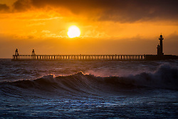 © Licensed to London News Pictures. 25/03/2019. Whitby UK. Strong winds whip up the sea as the sun rises this morning in Whitby on the Yorkshire coast. UK Photo credit: Andrew McCaren/LNP