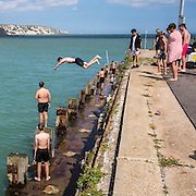A boy dives off Folkestone Harbour into the sea water with his friends watching after the annual Trawler race and fun day in Folkestone, Kent, England, United Kingdom. The White Cliffs of Dover can be seen in the background.  (photo by Andrew Aitchison / In pictures via Getty Images)
