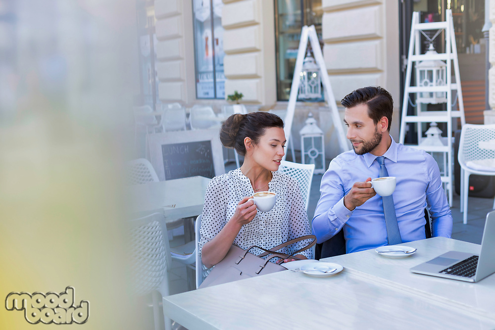 Businesswoman discussing plans with businessman while having coffee during office break