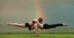 October 4, 2011 - Young woman balancing on top of man in prone position, practicing yoga in front of rainbow (Credit Image: © Image Source via ZUMA Press)