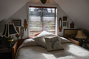 Comfy upstairs bedroom at Compass Rose Bed & Breakfast. Coupeville, Washington, USA. This fine 1890 Queen Anne Victorian home, on the National Register of Historic Places, is now an elegant two room bed and breakfast, furnished with antiques and glorious things from around the globe by the hosts, Captain and Mrs. Marshall Bronson.
