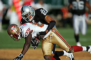 OAKLAND, CA - AUGUST 20:  Wide receiver Antonio Bryant #81 of the San Francisco 49ers gets tackled after catching a pass by cornerback Nnamdi Asomugha #21 of the Oakland Raiders at McAfee Coliseum on August 20, 2006 in Oakland, California. The Raiders defeated the Niners 23-7. ©Paul Anthony Spinelli *** Local Caption *** Antonio Bryant;Nnamdi Asomugha