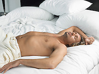 Partially nude man asleep on bed