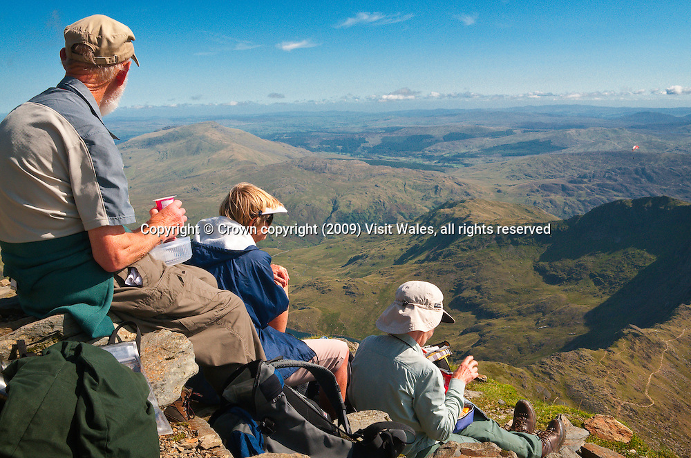Walkers resting at summit of Snowdon<br /> Snowdon / Yr Wyddfa<br /> Snowdonia<br /> North<br /> Walking<br /> Activities and Sports