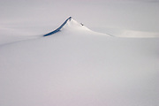 A pointed peak rises from the Greenland ice cap during a British mountaineering expedition to Knud Rasmussens Land, East Greenland, Arctic, 2006.