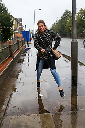 © Licensed to London News Pictures. 26/09/2019. London, UK. A woman jumps over a puddle of water gathered on the pavement on Seven Sisters Road in Finsbury Park, north London following heavy downpour early this morning. Photo credit: Dinendra Haria/LNP Photo credit: Dinendra Haria/LNP