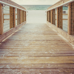 Pensacola Florida wooden boardwalk walkway photo at Casino Beach. Pensacola Beach is on Santa Rosa Island in the Emerald Coast region of the Southeastern United States. Photo is vertical and high resolution. Copyright ⓒ 2018 Paul Velgos with All Rights Reserved.