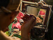 """26 NOVEMBER 2014 - BANGKOK, THAILAND: A performer puts on his makeup before a Chinese opera performance at the Chow Su Kong Shrine in the Talat Noi neighborhood of Bangkok. Chinese opera was once very popular in Thailand, where it is called """"Ngiew."""" It is usually performed in the Teochew language. Millions of Chinese emigrated to Thailand (then Siam) in the 18th and 19th centuries and brought their culture with them. Recently the popularity of ngiew has faded as people turn to performances of opera on DVD or movies. There are about 30 Chinese opera troupes left in Bangkok and its environs. They are especially busy during Chinese New Year and Chinese holidays when they travel from Chinese temple to Chinese temple performing on stages they put up in streets near the temple, sometimes sleeping on hammocks they sling under their stage.      PHOTO BY JACK KURTZ"""
