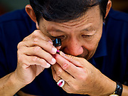 22 DECEMBER 2018 - CHANTABURI, THAILAND: A Thai gem buyer grades gems brought to him in the gem market in Chantaburi. The gem market in Chantaburi, a provincial town in eastern Thailand, is open on weekends. Chantaburi used to be an active gem mining area in Thailand, but the mines are played out now. Now buyers and sellers come from around the world to Chantaburi for the weekend market. Many of the stones come from Myanmar, others come from mines in Afghanistan and Africa.      PHOTO BY JACK KURTZ