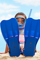 Girl (7-9 years) sitting in flippers and snorkling mask on beach