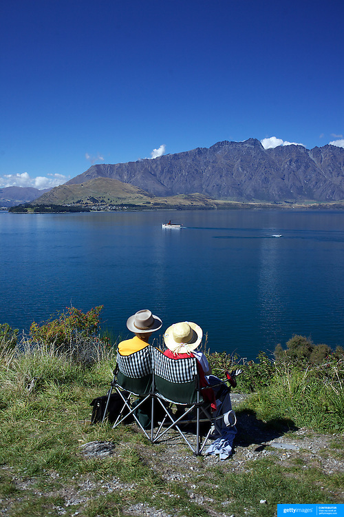 An elderly couple watch the TSS Earnslaw cruise past The Remarkables Mountain Range at Queenstown, New Zealand. .The TSS Earnslaw,  a 1912 Edwardian vintage twin screw steamer on the waters of Lake Wakatipu in, Queenstown, New Zealand. .It is one of the oldest tourist attractions in Central Otago, and the only remaining passenger-carrying coal-fired steamship in the southern hemisphere..The TSS Earnslaw heads along Lake Wakatipu from Queenstown  daily, running tourist trips to Walter Peak Station passing magnificent  peaks and contrasting shoreline foliage along the lakeside. Queenstown, New Zealand. 12th March 2011. Photo Tim Clayton