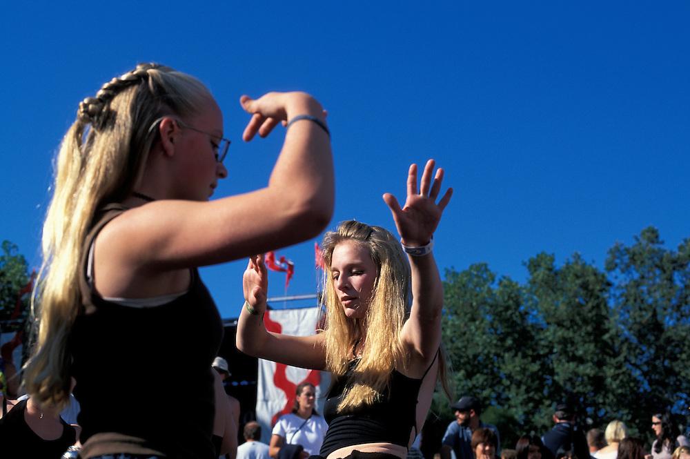 USA, Washington, Seattle, Tahlia Grant dances to sound of drum circle during Bumbershoot Festival in summer sunshine