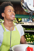 African American male store clerk weighing bell pepper
