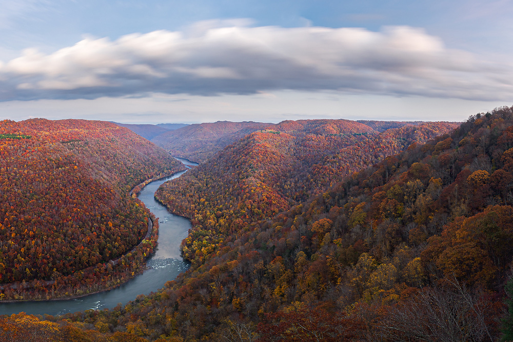 Large late evening clouds sweep across the mountains of Grandview State Park in West Virginia cloaked in colorful warm autumnal foliage contrasting with the deep blues of the New River, signifying the shifting seasons.