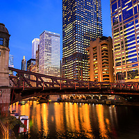 Photo of Chicago at night at Clark Street Bridge with downtown Chicago office buildings along the Chicago River.