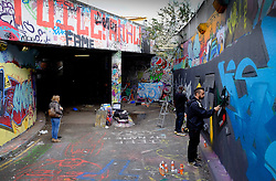 Graffiti artists decorating a wall in Leake Street in Waterloo. London