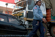A Cambodian policeman walks near a head on collision between a car and a truck on National Road 7 in Kampong Cham, Cambodia.