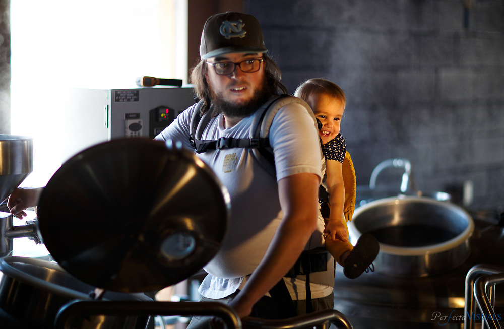 Sydney Preyer, 19 months old, yanks on her father's hair while at work with her father Calder Preyer at Preyer Brewing, Tuesday, October 20, 2015, in Greensboro, N.C. <br /> <br /> JERRY WOLFORD and SCOTT MUTHERSBAUGH / Perfecta Visuals<br /> <br /> Calder Preyer: &ldquo;I thought to myself &ndash; I love drinking beer; I should make it.&rdquo;<br /> <br /> Bio:&nbsp;Calder spent the last 10 years brewing beer at home and going to Chicago&rsquo;s Siebel Institute for brewing beer.<br /> &nbsp;<br /> Today, he is the brewmaster of Preyer Brewing, a local brewery he owns with his brothers, wife and parents. &ldquo;It&rsquo;s part art, it&rsquo;s part science,&rdquo; says Calder. Brewing beer is finding the perfect balance between chemistry, biology, recipe formulation and technique.<br /> &nbsp;