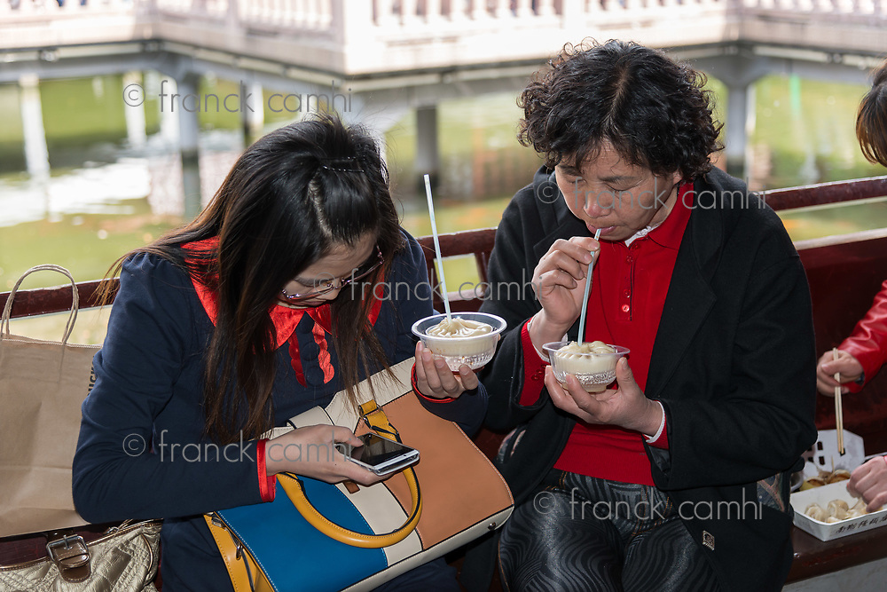 Shanghai, China - April 7, 2013: people eating dim sum Shanghai style steamed pork dumplings at the Nanxiang Steamed bun shop in Fang Bang Zhong Lu old city at the city of Shanghai in China on april 7th, 2013