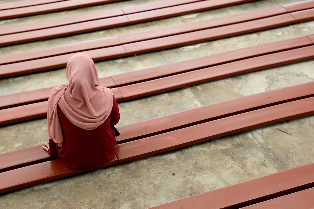 A woman sits amongst a row of bench seats at Singapore Zoo, Singapore.