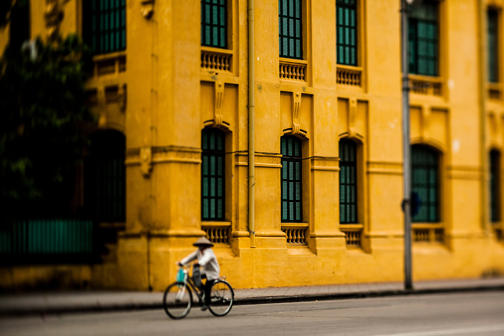 A woman rides by the Lycee Albert Sarraut building in Ba Dinh Square in Hanoi, Vietnam.