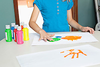 Mid section of a young girl finger painting on paper at table