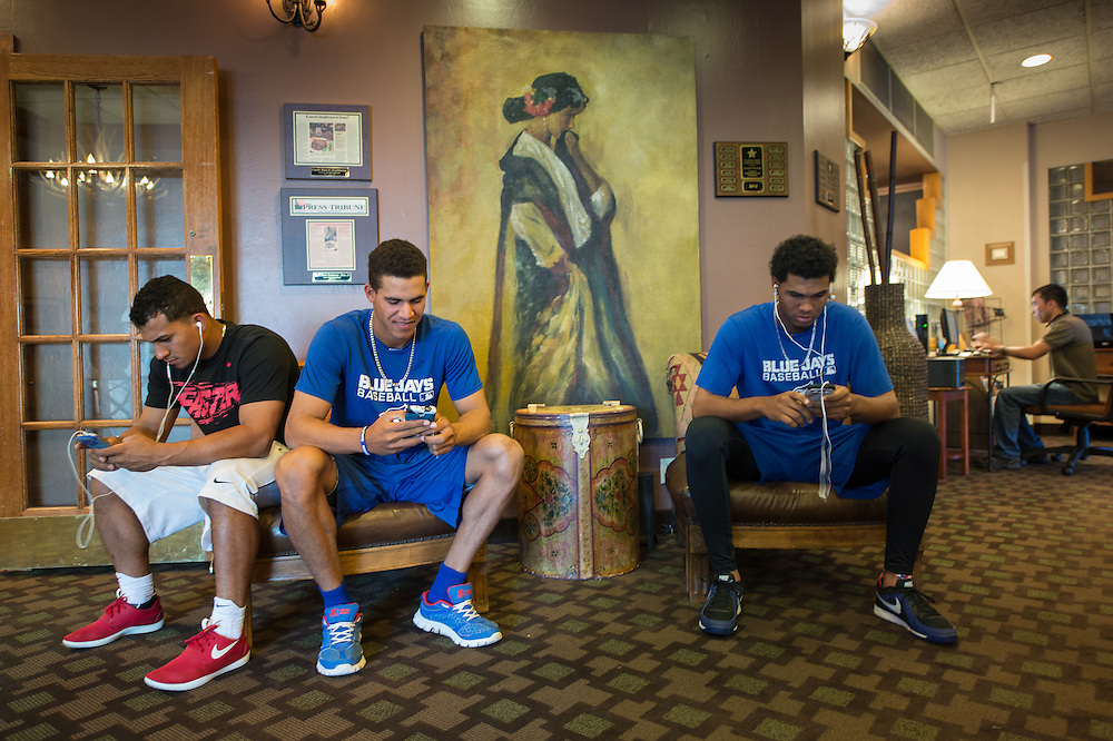 The Vancouver Canadians (left-right) Franklin Barreto, Jose Fernandez, and Yeyfry Del Rosario checking their electronic devices in the hotel lobby, waiting for the bus, on their way to work out at the gym while on the road in Boise, Idaho.