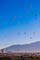 Hot air balloons flying (with the Sandia Mountains in background) at the Albuquerque International Balloon Fiesta, Albuquerque, New Mexico USA.