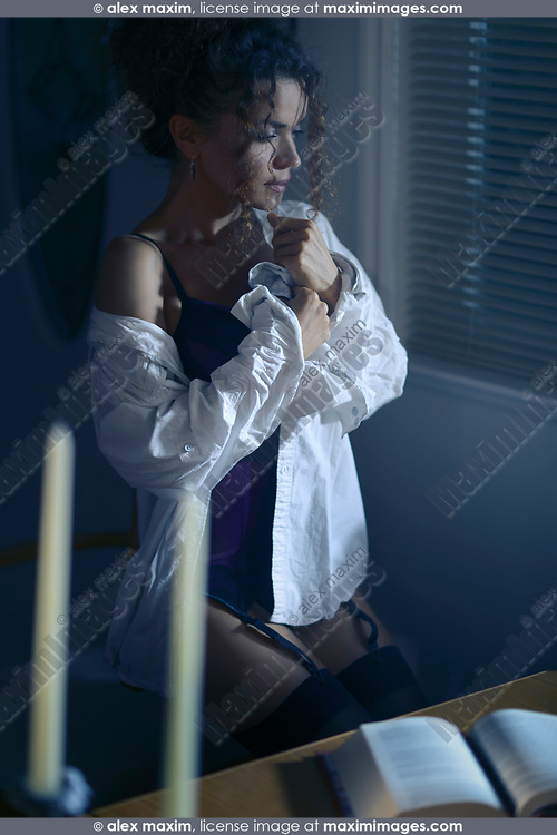 Sensual portrait of a beautiful young woman in a men's shirt on top of a sexy corset sitting by the window with a thoughtful expression at night in a dark room lit by street lights