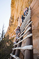 A woman poses for a picture on a ladder leading up to Balcony House cliff dwelling in Mesa Verde National Park, Colorado, USA.
