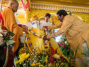 """09 SEPTEMBER 2013 - BANGKOK, THAILAND: A Buddhist monk, left, and a Hindu priest, anoint a statue of Ganesha at Shiva Temple in Bangkok. Ganesha Chaturthi also known as Vinayaka Chaturthi, is the Hindu festival celebrated on the day of the re-birth of Lord Ganesha, the son of Shiva and Parvati. The festival, also known as Ganeshotsav (""""Festival of Ganesha"""") is observed in the Hindu calendar month of Bhaadrapada. The date usually falls between 19 August and 20 September. The festival lasts for 10 days, ending on Anant Chaturdashi. Ganesha is a widely worshipped Hindu deity and is revered by many Thai Buddhists. Ganesha is widely revered as the remover of obstacles, the patron of arts and sciences and the deva of intellect and wisdom.     PHOTO BY JACK KURTZ"""