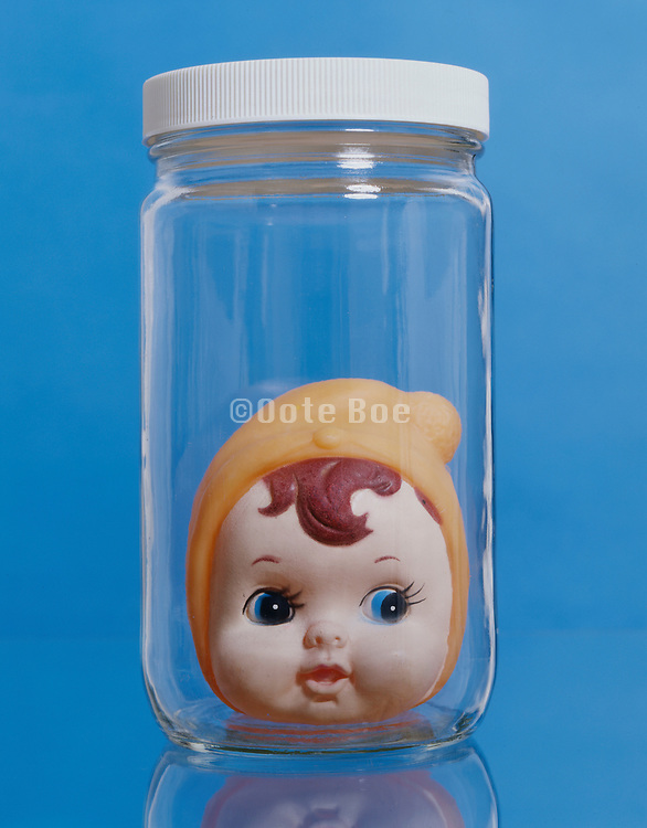 plastic doll head in glass jar against a blue background.