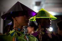 Models for the Brazilian brand, Neon, wearing plastic conical Asian-influenced hats wait backstage at São Paulo Fashion Week for Summer Season 2013/2014, at Bienal, in São Paulo, Brazil, on Wednesday, March 20, 2013.