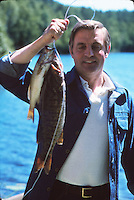 Walter Mondale fishing in Minnesota, having just caught a walleye
