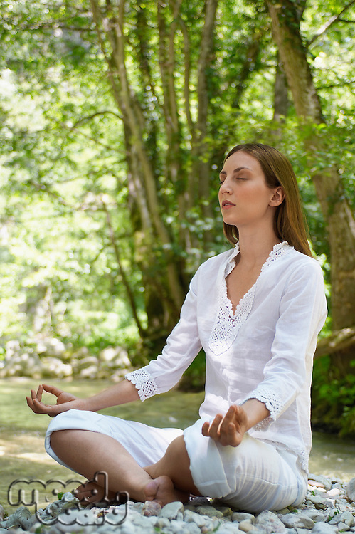 Young woman meditating by forest river full length