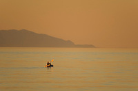 A mother and child at twilight, kayak into the peaceful waters of Georgia Strait just off of Goose Spit Regional Park.  Comox, The Comox Valley, Vancouver Island, British Columbia, Canada.