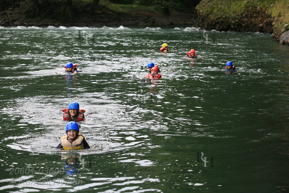 Ecoteach families take dip in Sarapiqui River at start of whitewater raft trip; Las Horquetas, Costa Rica.