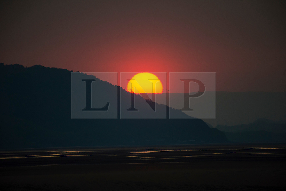 © London News Pictures. Dyfi Valley, Wales. Sunrise over the Dyfi estuary and distant windfarms  on the southern edge of Snowdonia National Park in Mid Wales UK. The weather today is forecast to be cloudier and cooler than over the weekend with outbreaks of rain, though north west wales and Scotland could still see temperatures in the mid 20's centigrade. Photo credit: Keith Morris/LNP