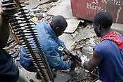 Liberian government gunman fix a jammed automatic weapon at the 'Old bridge' where they are holding back LURD (Liberians United for Reconciliation and Democracy) rebels from advancing accross the bridge to the capital Monrovia  24 July 2003. This is day six of continued fighting in the capital which has seen thousands displaced and more than 600 dead.The fighting is centered around 2 strategic bridges, the New and Old bridge, which provide access to the city.<br /> EPA PHOTO/NIC BOTHMA