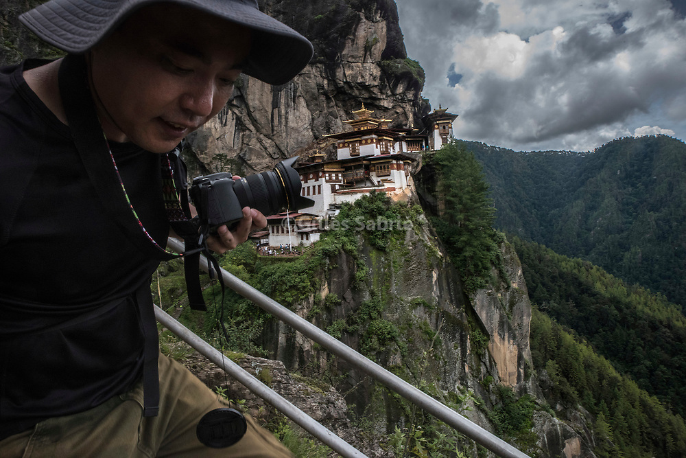 For a story by Steven Lee Myers, Bhutan<br /> Paro, Bhutan, August 4th, 2017<br /> Gu Huan, a 36 years old teacher from Lhassa (China), hiking towards the Dragon's Nest, a famous temple and the most visited site in Bhutan. In 2016 Chinese tourists topped the charts of dollar paying tourists in Bhutan. Tourism is a main contributor to Bhutan GDP. To get to Bhutan, Gu travelled overland from Lhassa to Kathmandu (Nepal) then flew from there to Paro, a 3 days trip. A direct flight from Lhassa to Paro would only take 45 minutes. There are no direct links between China and Bhutan and the two country have no official diplomatic ties. <br /> Gilles Sabri&eacute; pour The New York Times