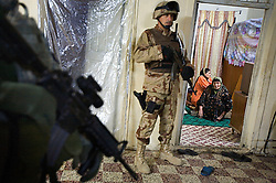 Iraqi soldiers and American troops search a home in a joint mission using intelligence gathered from captured insurgent Ahmed Mohammed Ali, also known as Neshuan, Mosul, Iraq, Dec. 12, 2005. Members of the 1st Infantry, 17th Regiment, helped Iraqi forces in preparation for Iraq's first  post-Saddam parliamentary elections. The western sector is home to Mosul's primarily Sunni population, which has been resistant to the American presence in Iraq.