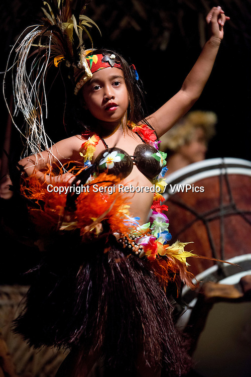 Rarotonga Island. Cook Island. Polynesia. South Pacific Ocean. Highland Paradise Cultural Village. A girl dressed in traditional cook island costumes dance during the Highland Paradise Cultural Village show. This 600 year old village site was home to the famous Tinomana Tribe but was abandoned in the early 1800s with the introduction of Christianity. The Pirangi family, descendants of the original High Chief Tinomana, has ensured the survival of this 205 acre mountain refuge by re-discovering and re-opening it to Cook Islanders and visitors alike. Now once again, you can experience the strong and meaningful spiritual bonds associated with the land, the maraes and the people (past and present) of this unique and colourful tribe. During your hours at Highland Paradise, you will discover ancient, significant places and examples of worship, chiefly council, warfare, sacrifice, tribal justice, home making, agriculture, medicines, fishing, education and canoe voyaging. We have reproduced buildings, re-installed artefacts and uncovered sites of great importance to our people. The 25 developed acres are but a tiny part of this site, but within this area you will relive the village as it was for more than 500 years. Native, introduced and medical plants are abundant and the gardens a delight to behold.