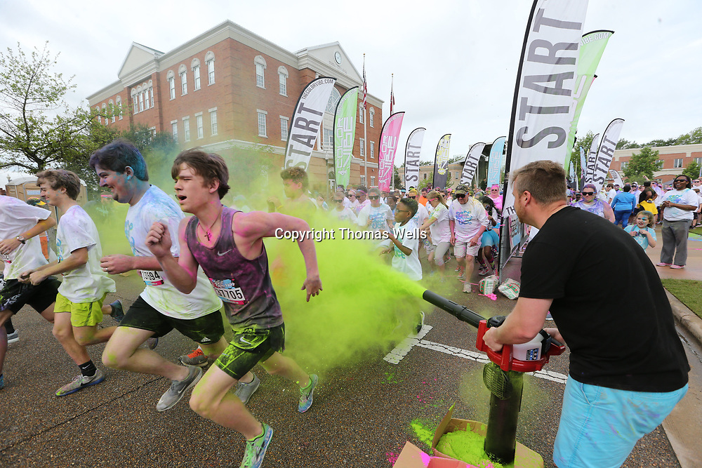 Groups of 200 runners make their way through a wall of color as they begin this year's Color Vibe 5K Run. The run had nearly 1,800 runners and the proceeds go to the Family Resource Center in Tupelo.