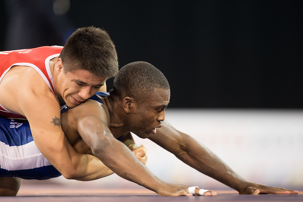 Ali Soto (top) of Mexico holds Dylan Williams of Canada in their quarter final bout in the 59kg class of the men's greco-roman wrestling at the 2015 Pan American Games in Toronto, Canada, July 15,  2015.  AFP PHOTO/GEOFF ROBINS