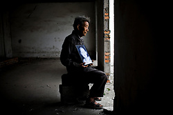 Grandfather Huang Qing Tai, 70, holding a picture of grandson Fu Hao, 11, is seen at Fuxin No.2 Primary  School in Wufu, Sichuan province May 25, 2008.  Fu Hao's  parents work in Gongdong so he and his wife takes care of grandson.