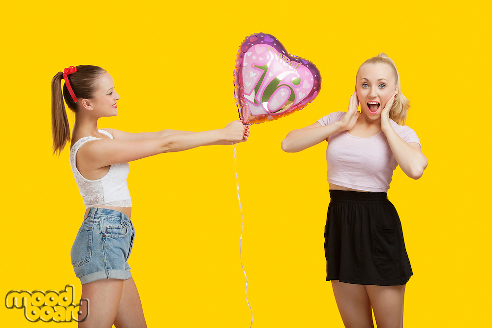 Happy young woman giving birthday balloon to amazed woman standing over yellow background
